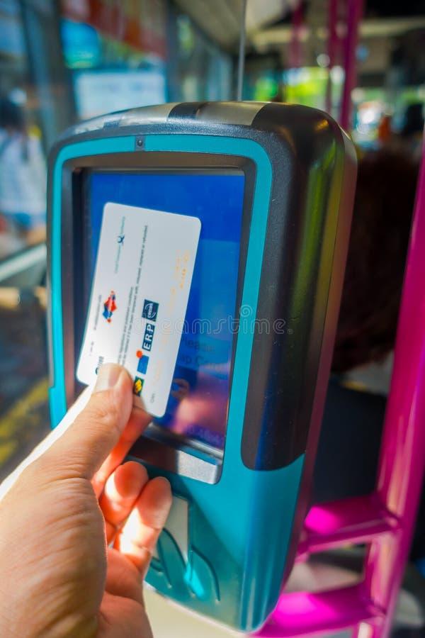 ΣΙΓΚΑΠΟΎΡΗ, ΣΙΓΚΑΠΟΎΡΗ - 1 ΦΕΒΡΟΥΑΡΊΟΥ 2018: Εσωτερική άποψη ενός προσώπου που χρησιμοποιεί μια κάρτα για να πληρώσει για τις δημ στοκ εικόνα