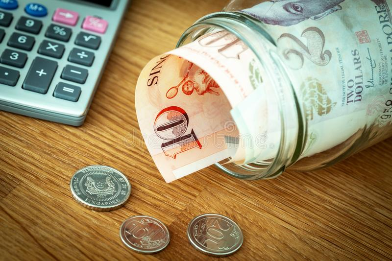 Σιγκαπούριος χρήματα, διάφοροι λογαριασμοί δολαρίων που κρατιούνται στο βάζο στοκ εικόνες