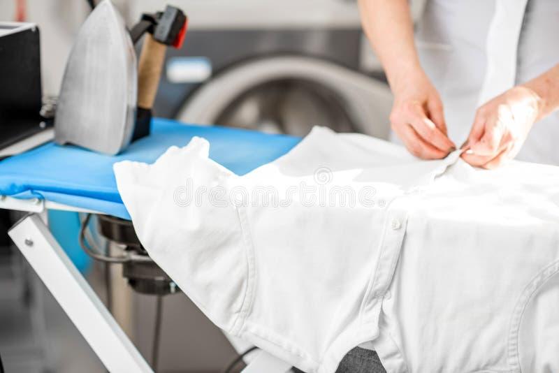 Σιδέρωμα ενός άσπρου πουκάμισου στον πίνακα στοκ εικόνες