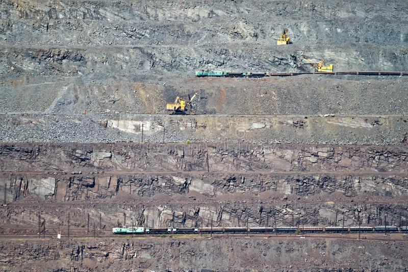 Σιδηρομετάλλευμα φόρτωσης εκσκαφέων στο βαγόνι εμπορευμάτων αγαθών στο υπαίθριο ορυχείο σιδηρομεταλλεύματος στοκ εικόνα με δικαίωμα ελεύθερης χρήσης