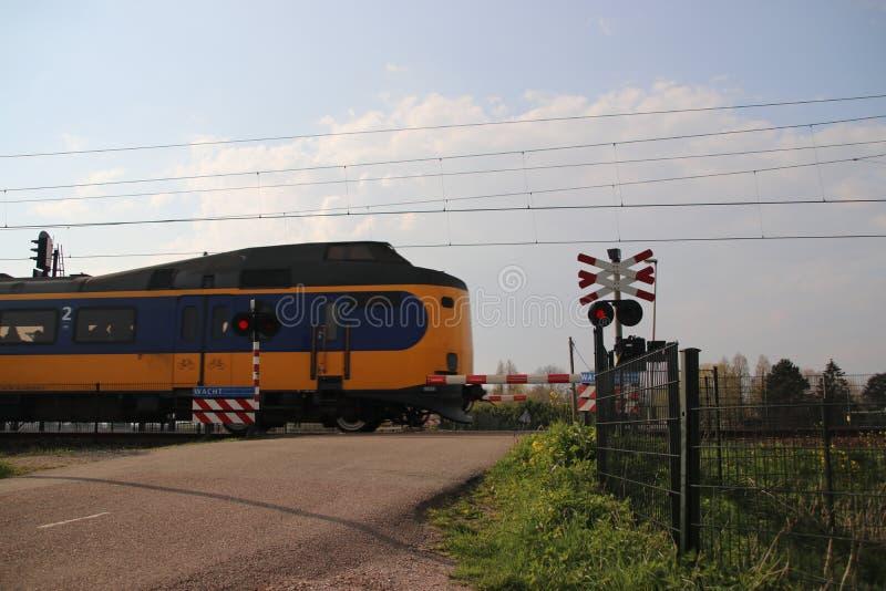Σιδηρόδρομος που διασχίζει με τα εμπόδια και τα κόκκινα φώτα με ICM intercity τραίνο koploper σε Moordrecht στις Κάτω Χώρες στοκ φωτογραφία με δικαίωμα ελεύθερης χρήσης