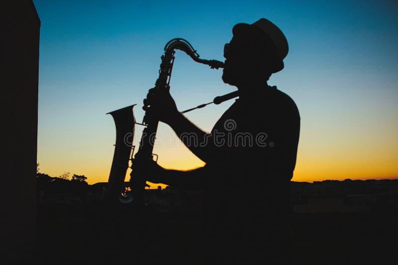 Σιλουέτα ενός άνδρα που παίζει σαξόφωνο κατά τη διάρκεια του Sunset στοκ φωτογραφία με δικαίωμα ελεύθερης χρήσης