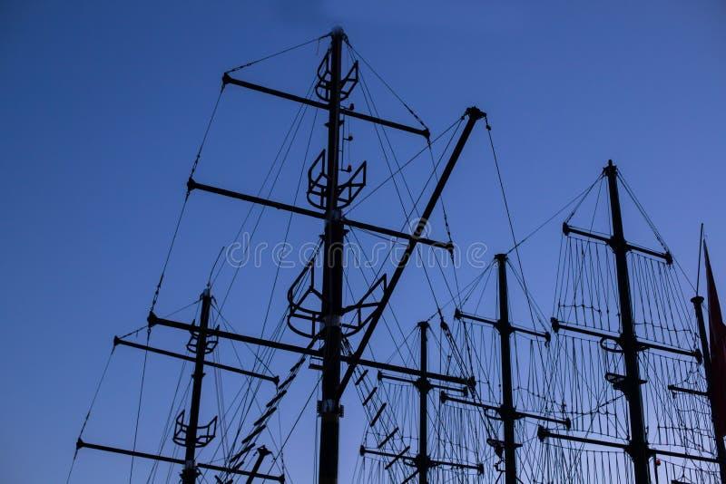 Σιλουέτες από φεγγαρόπετρες ενάντια στον γαλάζιο ουρανό το βράδυ Ιστιοφόρο το σούρουπο Ιστοί πειρατικού πλοίου στο σκοτάδι Διαβάθ στοκ φωτογραφία με δικαίωμα ελεύθερης χρήσης