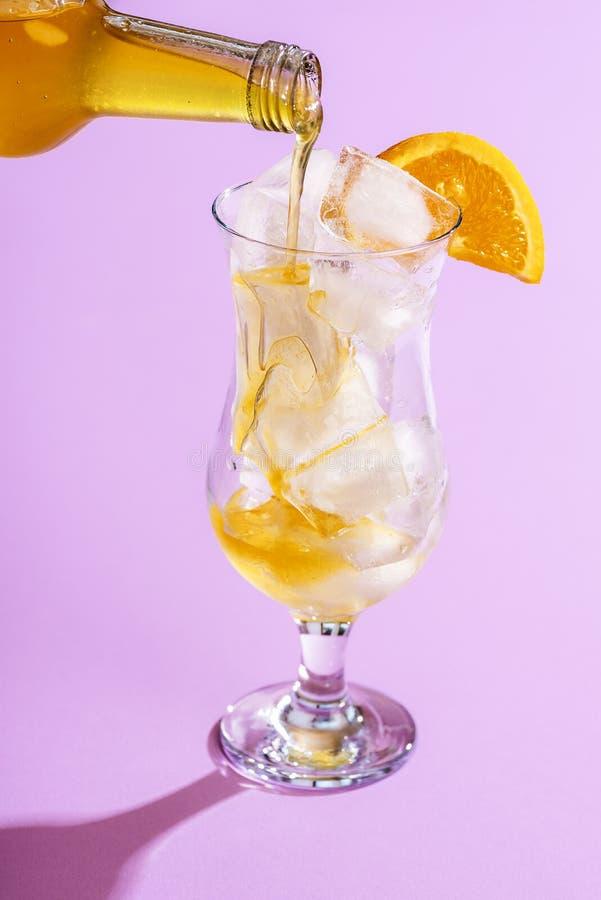 Σιρόπι πορτοκαλί σε ποτήρι με παγάκια Κατασκευή λεμονάδα στοκ εικόνα