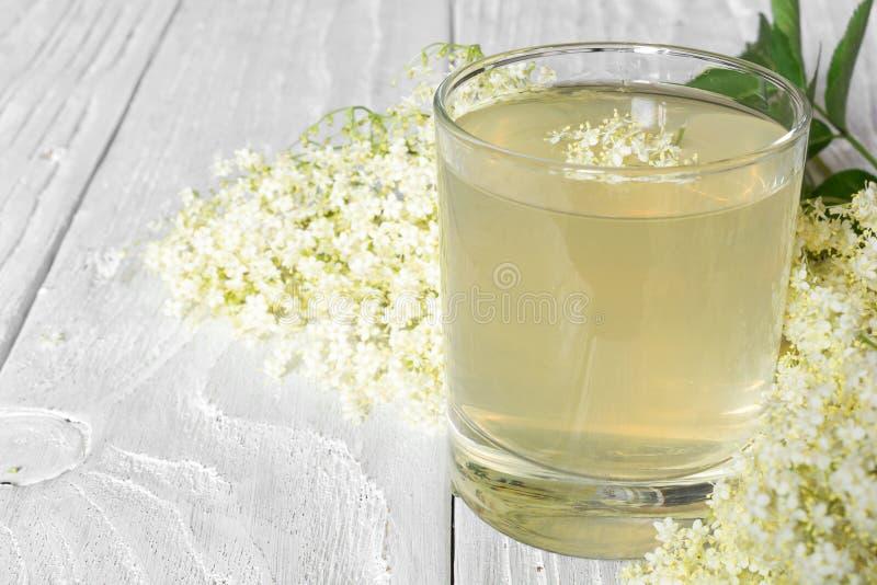 Σιρόπι Elderflower με τα λουλούδια στον άσπρο ξύλινο πίνακα υγιές βοτανικό ποτό στοκ φωτογραφίες
