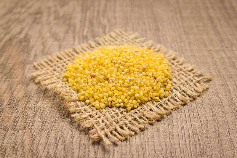Σιτάρι δημητριακών κεχριού Proso Σιτάρια στην τετραγωνική διακοπή της γιούτας Ξύλο στοκ εικόνα με δικαίωμα ελεύθερης χρήσης