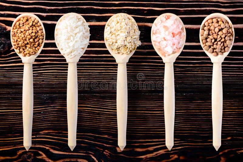 Σιτάρι διαφορετικών δημητριακών στα ξύλινα κουτάλια ενάντια στο ξύλινο backgrou στοκ φωτογραφίες