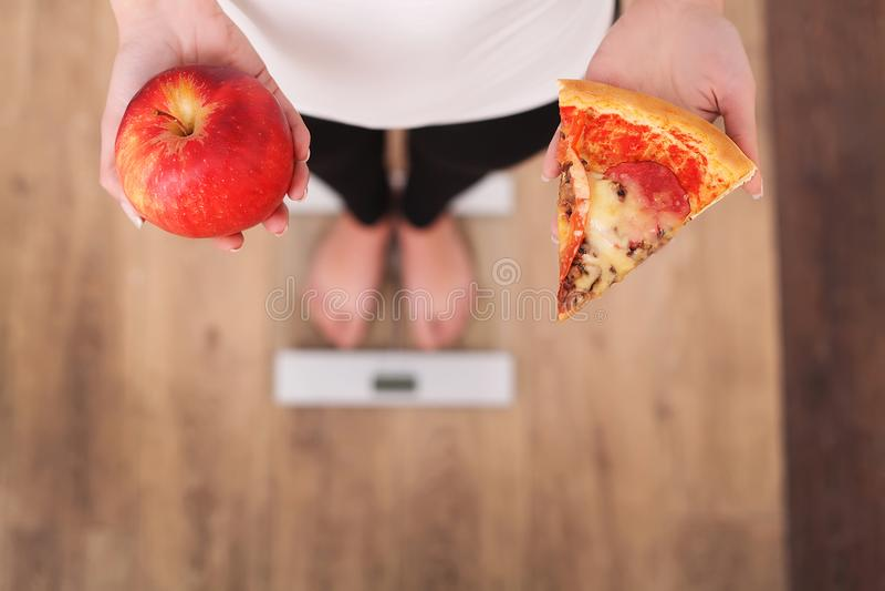 σιτηρέσιο Γυναίκα που μετρά το βάρος σώματος στην πίτσα εκμετάλλευσης ζυγού Τα γλυκά είναι ανθυγειινό άχρηστο φαγητό Κάνοντας δία στοκ εικόνα