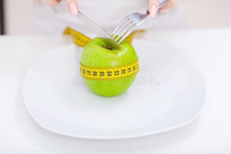 σιτηρέσιο Κλείστε επάνω τη φωτογραφία του μέτρου ταινιών που κουλουριάζεται γύρω από ένα μήλο στο W στοκ εικόνες