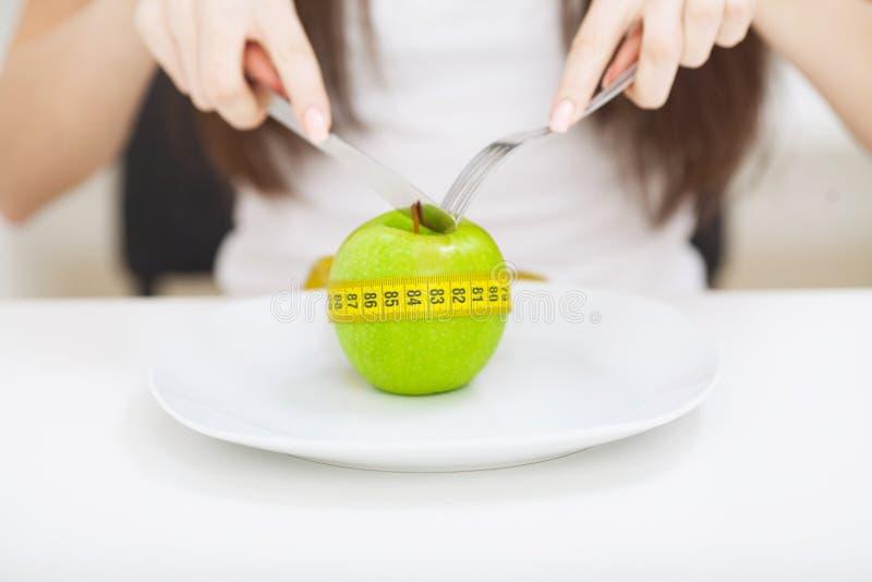 σιτηρέσιο Κλείστε επάνω τη φωτογραφία του μέτρου ταινιών που κουλουριάζεται γύρω από ένα μήλο στο W στοκ φωτογραφία με δικαίωμα ελεύθερης χρήσης