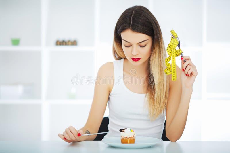 σιτηρέσιο Το πεινασμένο κορίτσι γυναικών με την κίτρινη μετρώντας ταινία κρατά υπό εξέταση στοκ εικόνα