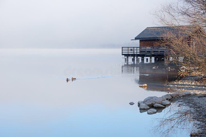 Σιωπηλό πρωί στο schliersee ακτών λιμνών με το boathouse και την ομίχλη στοκ εικόνα με δικαίωμα ελεύθερης χρήσης