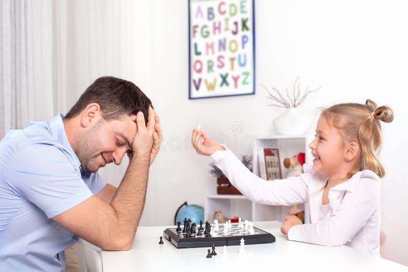 Σκάκι παιχνιδιού μικρών κοριτσιών και μπαμπάδων σε έναν πίνακα σε ένα δωμάτιο Είναι καλοί μαζί, είναι ευτυχείς στοκ εικόνες