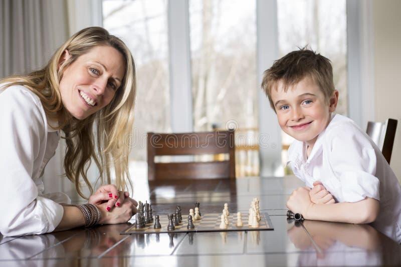 Σκάκι παιχνιδιού αγοριών στο σπίτι με τη μητέρα στοκ εικόνες με δικαίωμα ελεύθερης χρήσης