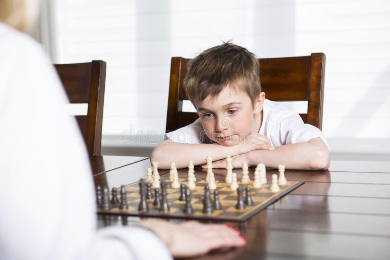 Σκάκι παιχνιδιού αγοριών στο σπίτι με τη μητέρα στοκ φωτογραφία με δικαίωμα ελεύθερης χρήσης