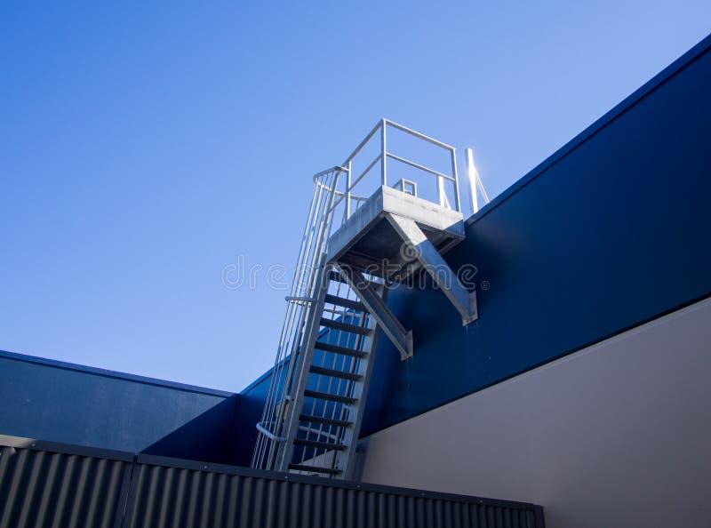 Σκάλα πυρκαγιάς κλουβιών χάλυβα στην κορυφή στεγών του κτηρίου στοκ εικόνες με δικαίωμα ελεύθερης χρήσης