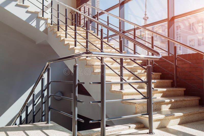 Σκάλα στο σύγχρονο κτήριο εμπορικών κέντρων Έξοδος κινδύνου Σκαλοπάτια στο εμπορικό κέντρο Άσπρη σκάλα από το παράθυρο στοκ εικόνα