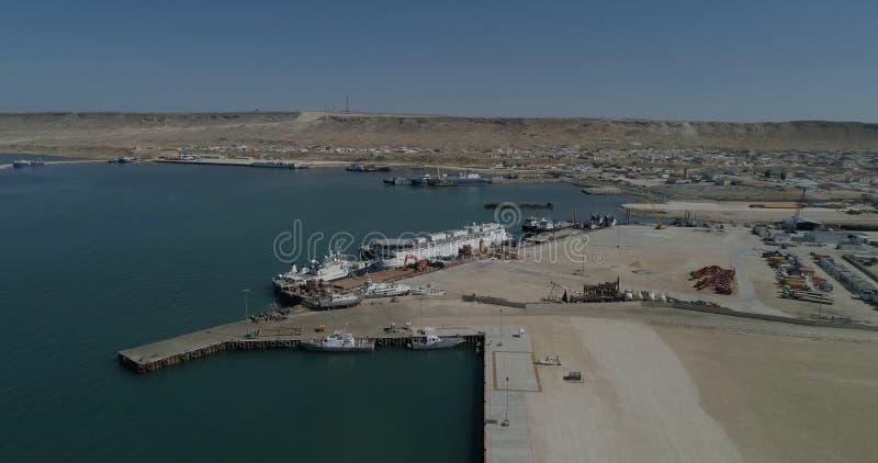 Σκάφη εμπορευματοκιβωτίων - που καθορίζονται στο λιμένα Bautino Καζακστάν στις ακτές της Κασπίας Θάλασσα Φόρτωση και εκφόρτωση στοκ φωτογραφία
