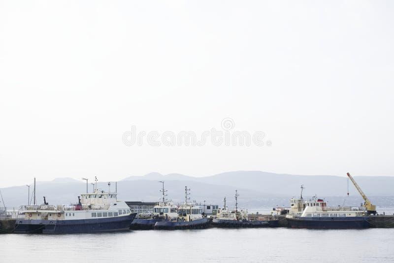 Σκάφη και βάρκες ρυμουλκών με το γερανό στην αποβάθρα θαλασσίων λιμένων στοκ φωτογραφία με δικαίωμα ελεύθερης χρήσης