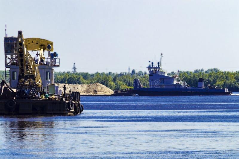 Σκάφος γερανών ποταμών που δένεται στην ακτή Στο υπόβαθρο, μια βάρκα ρυμουλκών ωθεί μια φορτηγίδα με την άμμο στοκ εικόνες