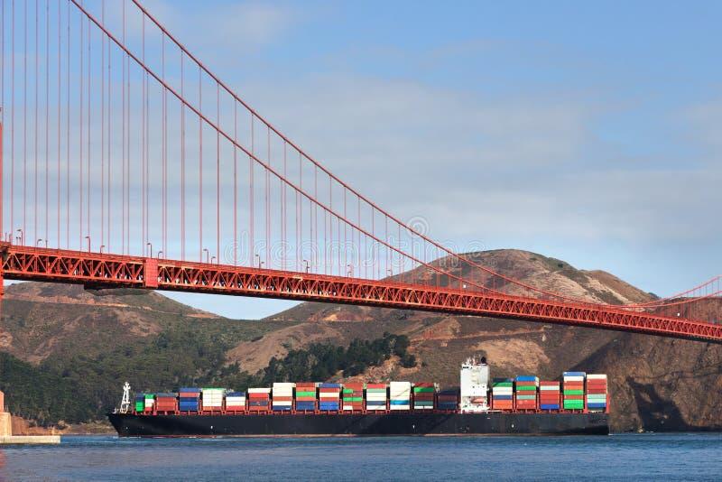Σκάφος εμπορευματοκιβωτίων κάτω από τη χρυσή γέφυρα πυλών στοκ φωτογραφίες με δικαίωμα ελεύθερης χρήσης
