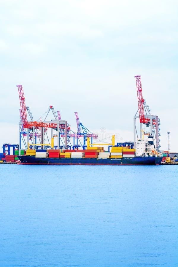 Σκάφος εμπορευματοκιβωτίων στο θαλάσσιο λιμένα Ο γερανός λιμένων φορτώνει ένα εμπορευματοκιβώτιο σε ένα σκάφος στοκ εικόνα με δικαίωμα ελεύθερης χρήσης