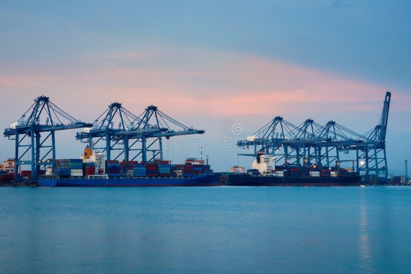Σκάφος φορτίου φορτίου εμπορευματοκιβωτίων με τη λειτουργώντας γέφυρα γερανών στο ναυπηγείο στο σούρουπο για τη λογιστική εισαγωγ στοκ φωτογραφίες με δικαίωμα ελεύθερης χρήσης