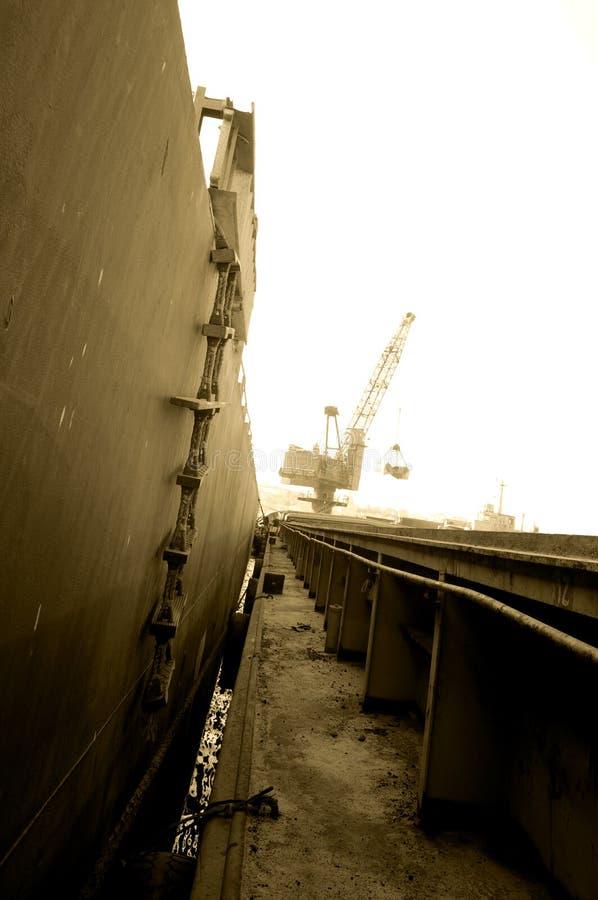 Σκάλα σχοινιών σκαφών με τους ξύλινους πίνακες, γερανός που λειτουργεί στο ηλιόλουστο υπόβαθρο - σέπια στοκ φωτογραφία