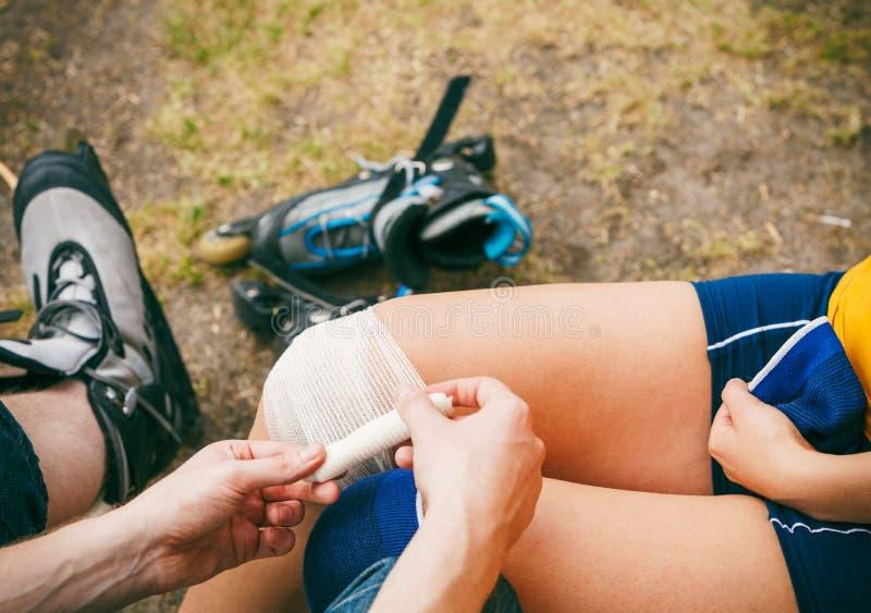Σκέιτερ γυναικών με το τραυματισμένο γόνατο ποδιών στοκ φωτογραφία