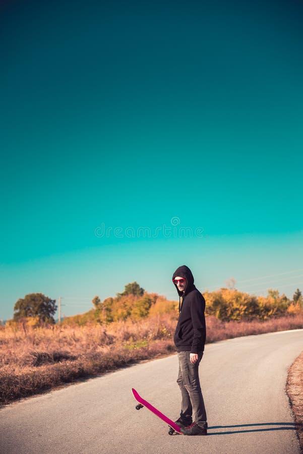 Σκέιτερ με ρόδινο skateboard στο δρόμο στοκ φωτογραφία