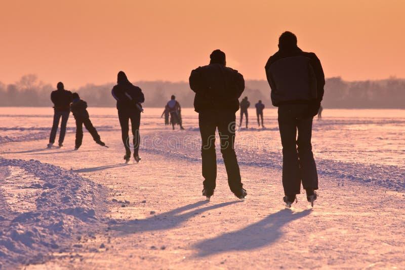 Σκέιτερ πάγου κάτω από τον ήλιο ρύθμισης στοκ εικόνα