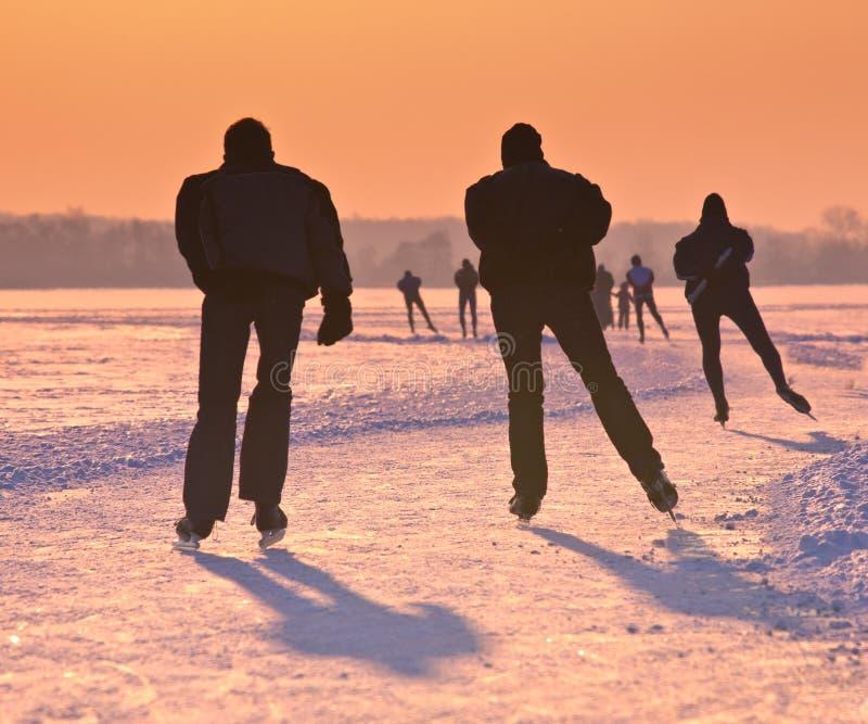 Σκέιτερ πάγου στην παγωμένη λίμνη στο ηλιοβασίλεμα στοκ φωτογραφίες