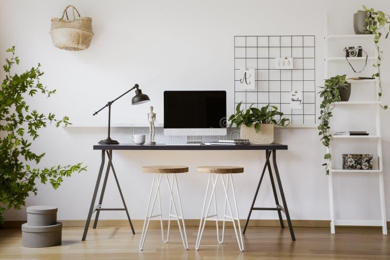 Σκαμνιά στο γραφείο με το λαμπτήρα και τον υπολογιστή γραφείου στο freelancer ` s μέσα στοκ φωτογραφία