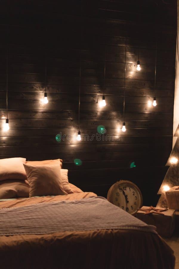 Σκανδιναβικό εσωτερικό κρεβατοκάμαρων ύφους κάτω από τα Χριστούγεννα Της υφής ξύλινο κρεβάτι στο ύφος αγροτικού του νέου έτους πο στοκ εικόνα με δικαίωμα ελεύθερης χρήσης