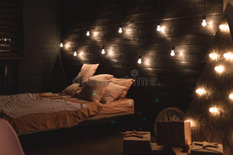 Σκανδιναβικό εσωτερικό κρεβατοκάμαρων ύφους κάτω από τα Χριστούγεννα Της υφής ξύλινο κρεβάτι στο ύφος αγροτικού του νέου έτους πο στοκ φωτογραφίες με δικαίωμα ελεύθερης χρήσης