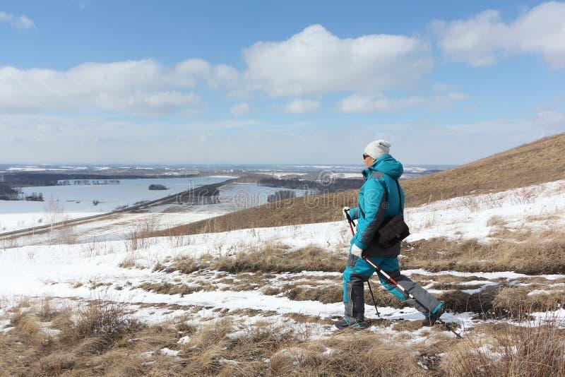 Σκανδιναβικό περπάτημα - ενήλικη γυναίκα που κατεβαίνει από το βουνό στοκ εικόνες με δικαίωμα ελεύθερης χρήσης