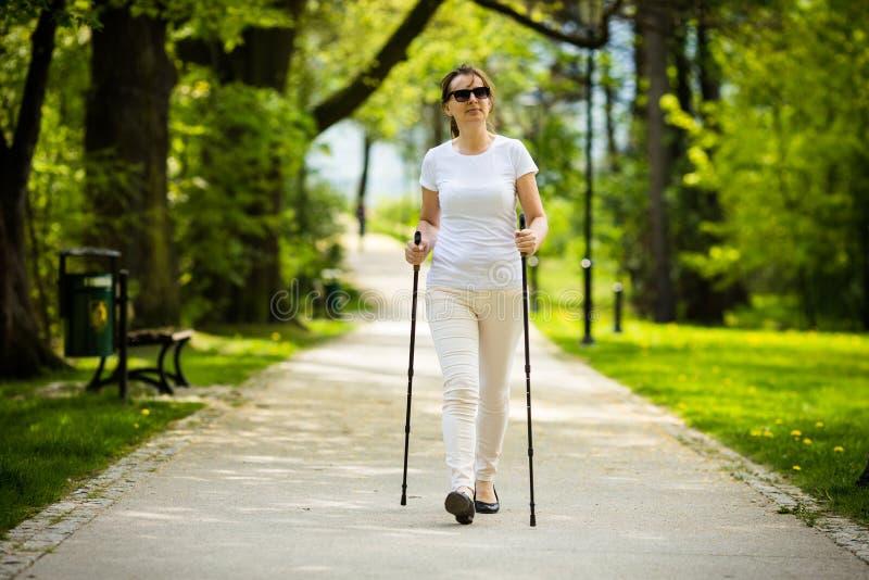 Σκανδιναβικό περπάτημα - μέσης ηλικίας επίλυση γυναικών στοκ εικόνες