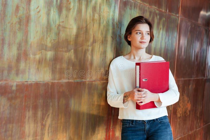 Σκεπτική αρκετά νέα γυναίκα που κρατά τον κόκκινο φάκελλο συνδέσμων δαχτυλιδιών στοκ εικόνα με δικαίωμα ελεύθερης χρήσης