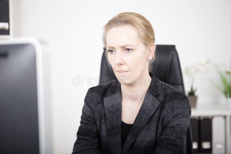 Σκεπτική γυναίκα γραφείων που εξετάζει τη οθόνη υπολογιστή στοκ εικόνα με δικαίωμα ελεύθερης χρήσης