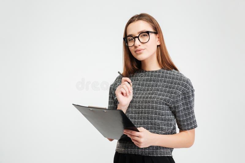 Σκεπτική νέα γυναίκα στα γυαλιά που κρατά την περιοχή αποκομμάτων και τη μάνδρα στοκ εικόνα