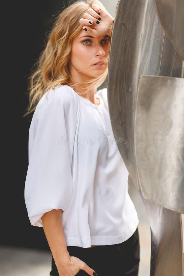 Σκεπτική νέα ξανθή γυναίκα με το χέρι σχετικά με το μέτωπό της στοκ φωτογραφία με δικαίωμα ελεύθερης χρήσης