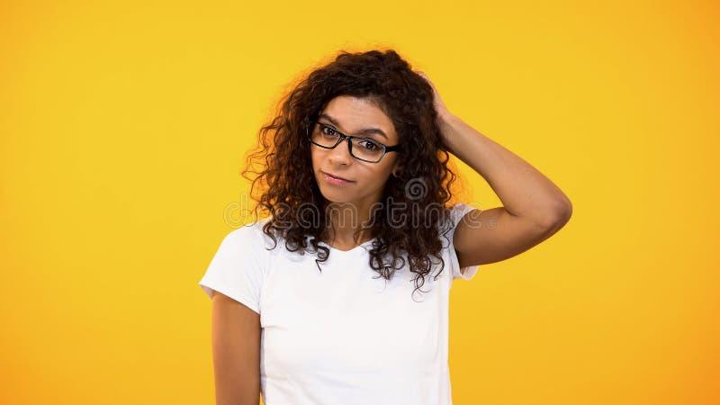 Σκεπτική biracial γυναίκα σχετικά με το πίσω μέρος του κεφαλιού, αβέβαιο της επιλογής, που λαμβάνει την απόφαση στοκ εικόνες
