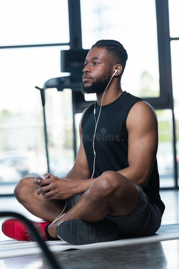 σκεπτικός αθλητικός τύπος αφροαμερικάνων στα ακουστικά χρησιμοποιώντας το smartphone και κοιτάζοντας μακριά καθμένος στο χαλί γιό στοκ φωτογραφίες με δικαίωμα ελεύθερης χρήσης