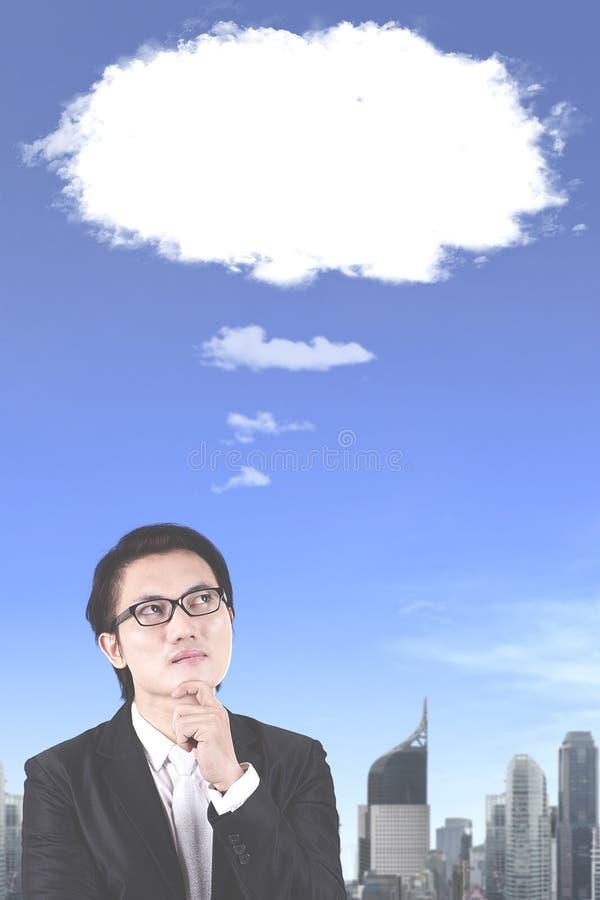 Σκεπτικός αρσενικός διευθυντής με την κενή φυσαλίδα σύννεφων στοκ φωτογραφία
