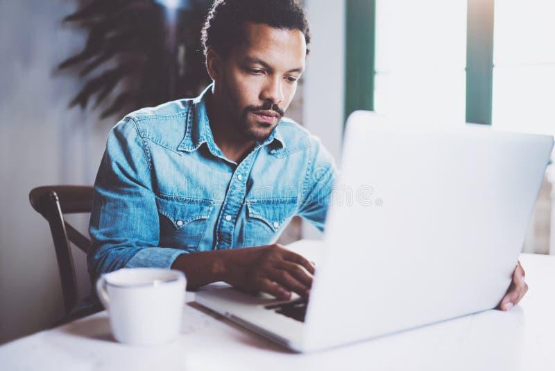 Σκεπτικός γενειοφόρος Αφρικανός που εργάζεται στο σπίτι καθμένος τον ξύλινο πίνακα Χρησιμοποίηση του σύγχρονου lap-top για τη νέα στοκ εικόνα