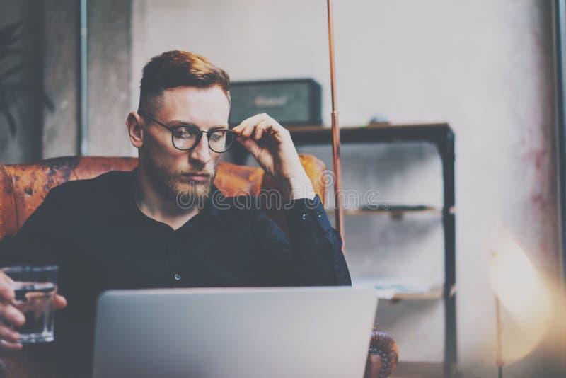 Σκεπτικός γενειοφόρος επιχειρηματίας eyeglasses που λειτουργούν στη σύγχρονη σοφίτα Συνεδρίαση ατόμων στην εκλεκτής ποιότητας καρ στοκ εικόνες