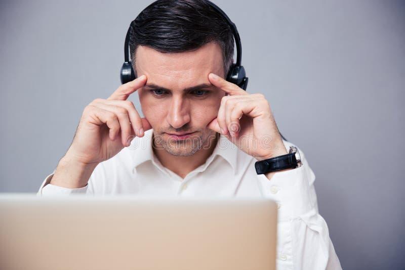 Σκεπτικός επιχειρηματίας που εργάζεται στο lap-top με τα ακουστικά στοκ εικόνες