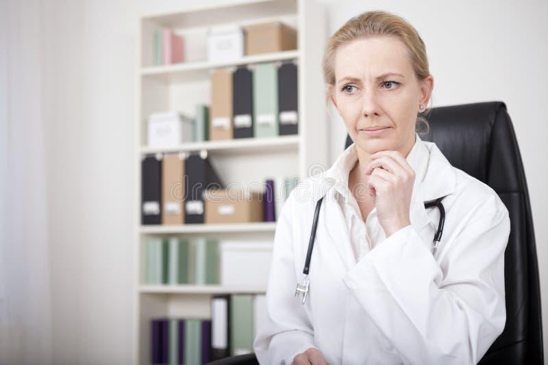 Σκεπτικός θηλυκός γιατρός με το χέρι στο πηγούνι της στοκ φωτογραφία με δικαίωμα ελεύθερης χρήσης