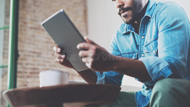 Σκεπτικό αφρικανικό άτομο που χρησιμοποιεί την ταμπλέτα για την τηλεοπτική συνομιλία χαλαρώνοντας στον καναπέ στο σύγχρονο γραφεί στοκ εικόνα