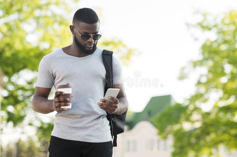 Σκεπτικό αφρικανικό άτομο χρησιμοποιώντας το κινητό τηλέφωνο και πίνοντας τον καφέ για να πάει στοκ εικόνα με δικαίωμα ελεύθερης χρήσης